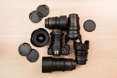 数字式SLR照相机和一些个互换性的手工透镜 电影摄制的设备 木表 免版税库存图片
