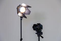 数字式SLR照相机和一盏聚光灯与一个菲涅耳透镜在灰色背景 在内部的射击 免版税图库摄影