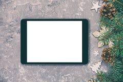 数字片剂嘲笑与土气应用程序介绍葡萄酒的圣诞节灰色水泥背景装饰,被定调子 顶视图与 库存照片