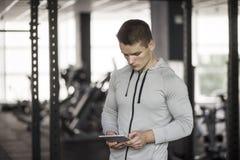 数字片剂的运动年轻人在训练在健身房前,使用与锻炼计划的应用 r 库存照片