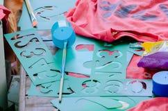数字的绿色样式与刷子和桃红色衬衣的在桌上 库存照片