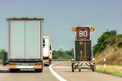 数字表明机动车路工地工作的交通标志与'please的德国词在显示 免版税库存照片