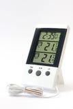 数字钟和一个数字体温计测量的温度的 库存照片