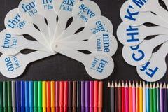 数字铅笔和卡片从一个的到十与字母表副本和辅音信件在黑学校黑板的 免版税库存图片