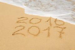 数字2016年和2017年在沙子 库存图片