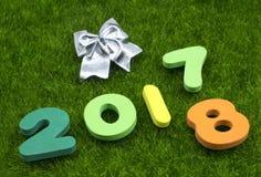 数字2017 2018年在与银色圣诞节弓的绿草 库存图片