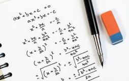 数学在考试、实践、测验或者测试的二次方程惯例手写顶视图在算术类 库存图片