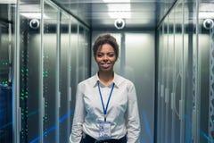 数据中心走廊的微笑的工程师  库存照片