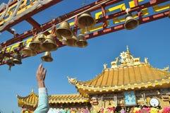敲响在藏传佛教寺庙前面的响铃 免版税图库摄影