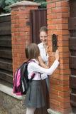 敲响在门铃和母亲开头Th的校服的女孩 免版税库存照片