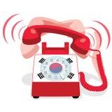 敲响的红色固定式电话有轮循拨号的和有韩国的旗子的 库存图片