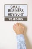 敲小企业情况通知门的商人 免版税库存图片