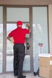敲门的送货人的背面图 免版税库存图片