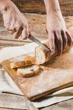 整个五谷面包投入了有拿着裁减的厨师的厨房木板材金刀子 库存照片