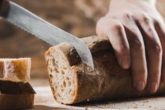 整个五谷面包投入了有拿着裁减的厨师的厨房木板材金刀子 免版税库存照片