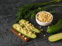 整个五谷面包用黄瓜和发芽的绿豆在村庄桌上 免版税库存照片
