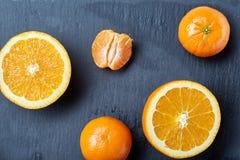 整个和半裁减新鲜的蜜桔和桔子平的位置在黑暗的背景,特写镜头 免版税库存图片