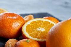 整个和半裁减新鲜的蜜桔和桔子特写镜头在切板在白色背景,浅景深 库存图片