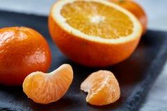 整个和半裁减新鲜的蜜桔和桔子特写镜头在切板在白色背景,浅景深 免版税库存照片