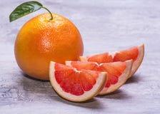 整个葡萄柚和切片,水多成熟在灰色背景 库存图片
