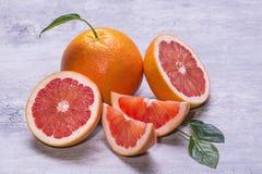 整个葡萄柚,一半和切片,绿色叶子,水多成熟在灰色背景 免版税库存照片