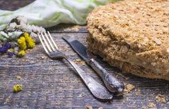 整个Naroleon,叉子和刀子蛋糕,装饰用在木背景的一块纺织品毛巾 免版税图库摄影