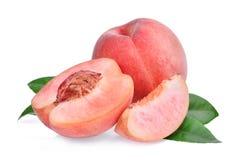 整体和一半与切片桃子与被隔绝的绿色叶子 免版税库存图片