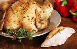整体烤了鸡用麝香草、胡椒和面包在木背景 图库摄影