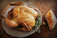 整体烤了鸡用麝香草和面包在木背景 免版税库存照片
