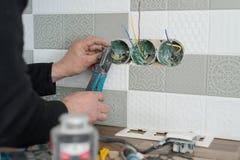 整修和建筑在厨房,电工特写镜头递安装出口在有瓷砖使用的墙壁 免版税库存照片
