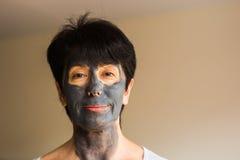 整容术、温泉、护肤和人概念-应用面部黏土面具的妇女 秀丽治疗 免版税库存图片