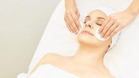 整容术医生从女孩面孔取消染睫毛油 化装棉用妇女手 Demakeup化妆水 免版税图库摄影