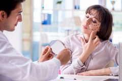 整形外科医生为在妇女面孔的操作做准备 免版税库存图片