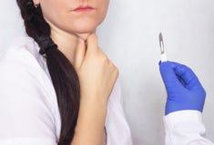 整形外科医生藏品解剖刀在她的以一个女孩为背景的手上有双下巴的双下巴的废弃 免版税库存照片