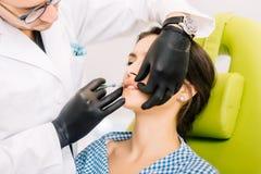 整形外科医生,使用嘴唇防皱治疗的医生射入和举技术 免版税库存照片