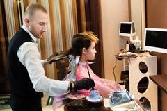整洁地穿戴了与女孩的头发,在他的手上的手套的发式专家工作 免版税库存图片