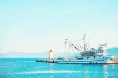 整洁的渔拖网渔船在一个小镇停泊了Postira -克罗地亚,海岛Brac的美丽的港口 库存图片