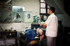 整理客户的理发师在一家小传统中国理发店 免版税库存照片