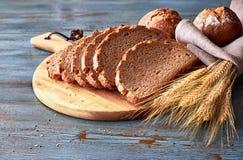整粒面包在船上切开了用rze小圆面包和金黄麦子耳朵 库存图片