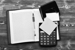 文具和皮革盖了笔记本,打开与空白页 组织者、计算器、穿孔机、便条纸和笔 图库摄影