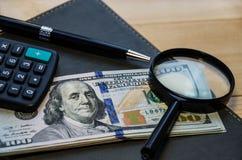 文具项目:美元、笔、计算器、放大器和笔记薄在一张木桌上 免版税库存图片