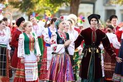 文化,哥萨克传统礼服的舞蹈家学院的学生队伍,上色了裙子、绿色长裤和褐紫红色 免版税库存照片