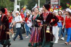 文化,哥萨克传统礼服的舞蹈家学院的学生队伍,上色了裙子、绿色长裤和褐紫红色 免版税库存图片