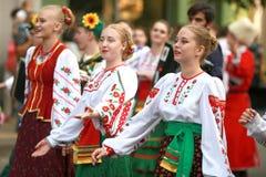 文化,哥萨克传统礼服的舞蹈家学院的学生队伍,上色了裙子、绿色长裤和褐紫红色 库存照片