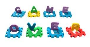 文字游戏组成由玩具塑料字母表难题被删去的信件,隔绝在白色背景 免版税库存图片