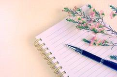 文字笔笔记本和花在甜颜色 免版税库存照片