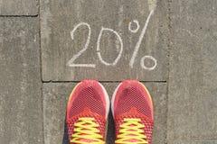 文本在与妇女腿的灰色路面从上面写的20%在运动鞋,看法 库存照片