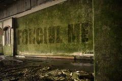 文本在肮脏的墙壁上原谅我在一个被放弃的被破坏的房子里 免版税库存照片