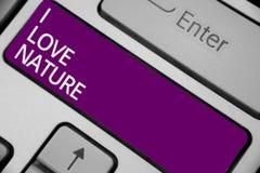 文本标志陈列我爱自然 概念性照片享受自然环境保存保护生态系键盘紫色钥匙 免版税库存照片