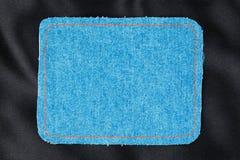 文本的框架从与橙色螺纹的被缝的线的一种蓝色牛仔裤织品 免版税库存照片